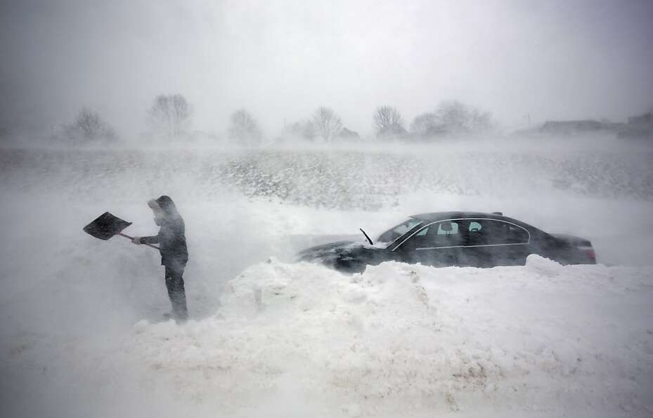 A woman digs out her car after it was blocked in by drifting snow during a blizzard, Saturday, Feb.