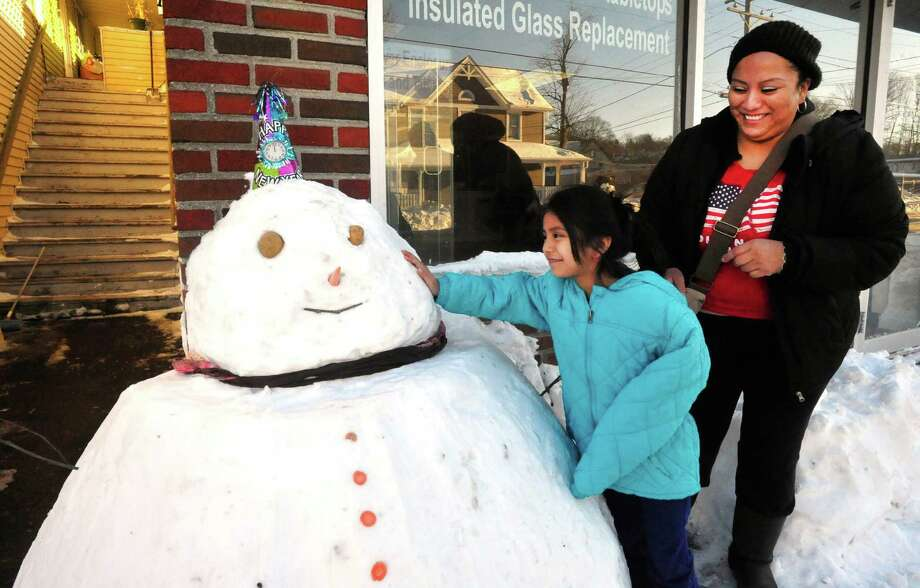 Karla Cando watches her daughter, Shirlyn, 6, play with a snowman in Danbury Saturday, Feb. 9, 2013. Photo: Michael Duffy / The News-Times