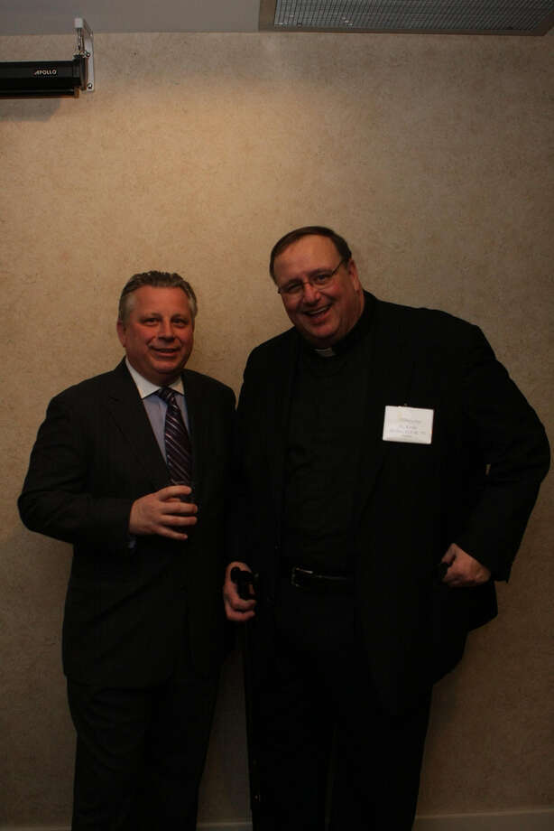 Howard Foote at a Siena College basketball reception with Father Kevin Mullen, the school's president.