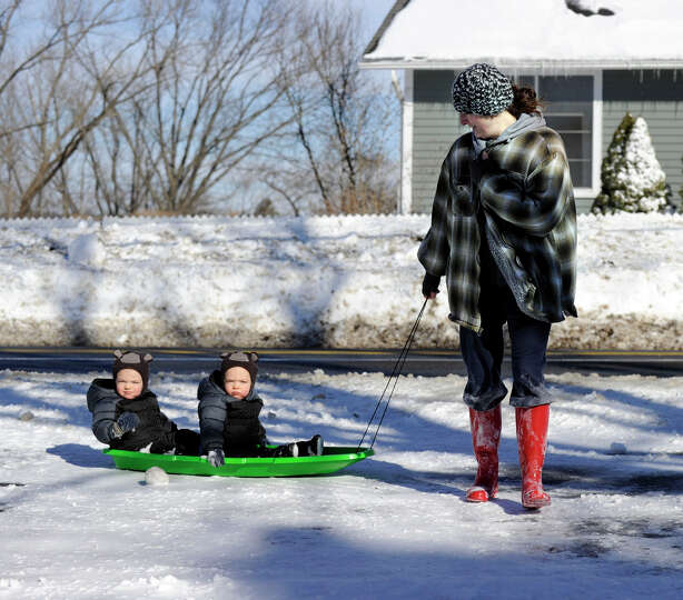 Genevieve Mulvaney pulls her twin sons on a sled around her home on Long Meadow Hill Road in Brookfi