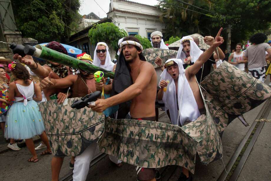"Revelers in costumes meant to resemble a military tank, one pointing a toy gun and another wearing a mask in the likeness of Osama bin Laden, perform during the ""Ceu na Terra"" block carnival parade in Rio de Janeiro, Brazil. Photo: AP"