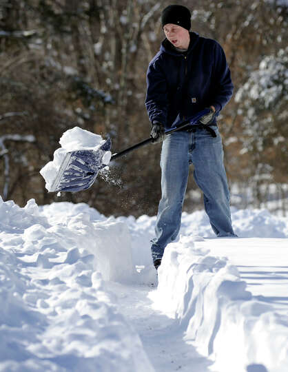 Jason Hanna, 24, shovels the driveway of his home on Hawleyville Road in Newtown, Conn. Saturday, Fe