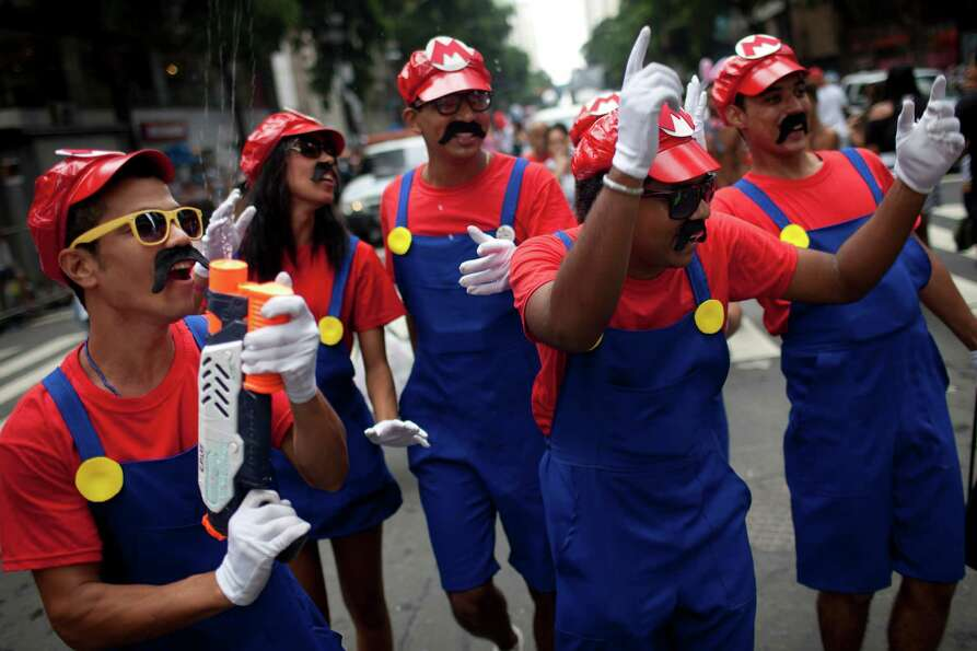 Revelers dressed as arcade character Mario Bros dance during the