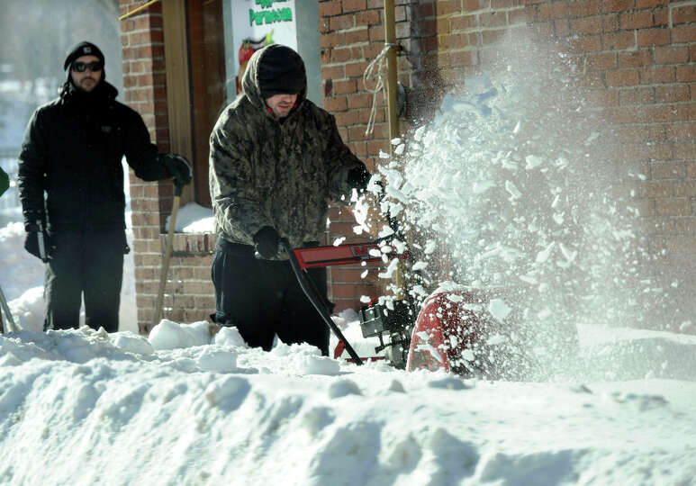 Workers clear the streets of snow in Danbury, Conn. Saturday after a blizzard dumped almost two feet