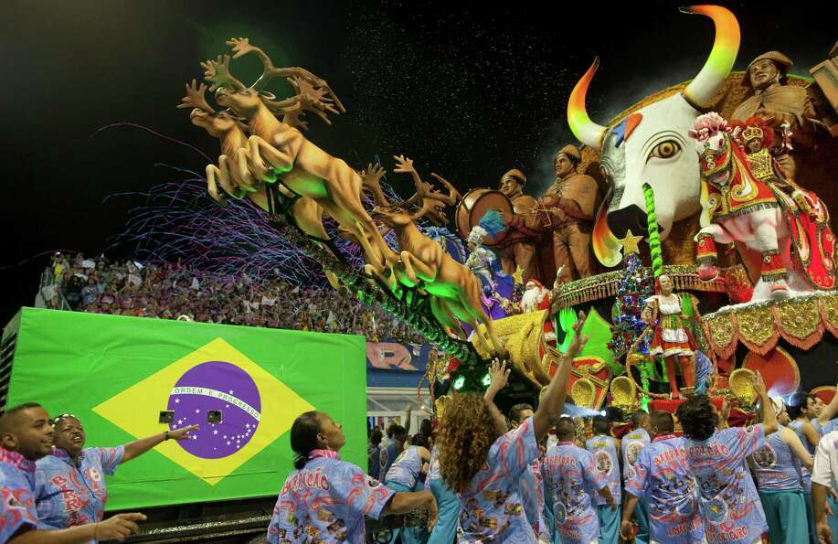 Dancers from the Rosas de Ouro samba school surround their float during a carnival parade in Sao Pau