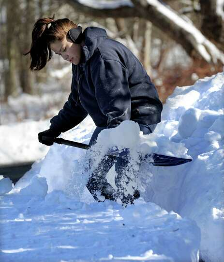 Andrea Hanna, 21, shovels the driveway of her home on Hawleyvilel Road in Newtown, Conn. Saturday, F