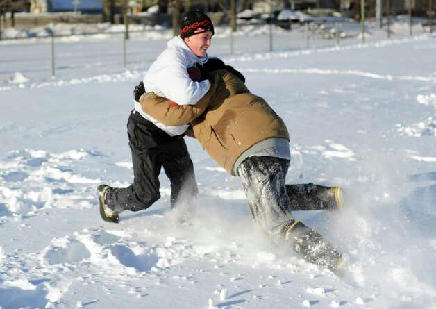 Timothy Mira, left, and Anthony Pampena Jr., right, play football in Cummings Park in Stamford, Conn., on Saturday, February 9, 2013. Photo: Lindsay Perry / Stamford Advocate