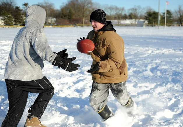 Mario Sciarretta, left, and Anthony Pampena Jr., right, play football in Cummings Park in Stamford, Conn., on Saturday, February 9, 2013. Photo: Lindsay Perry / Stamford Advocate