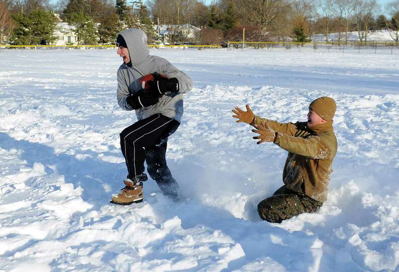 Mario Sciarretta, left, and Bobby Truong, right, play football in Cummings Park in Stamford, Conn.,