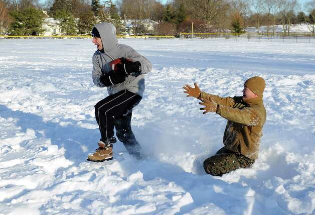 Mario Sciarretta, left, and Bobby Truong, right, play football in Cummings Park in Stamford, Conn., on Saturday, February 9, 2013. Photo: Lindsay Perry / Stamford Advocate
