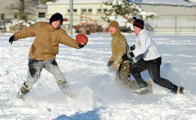 Anthony Pampena Jr., left, Bobby Truong, center, and Timothy Mira, right, play football in Cummings Park in Stamford, Conn., on Saturday, February 9, 2013. Photo: Lindsay Perry / Stamford Advocate