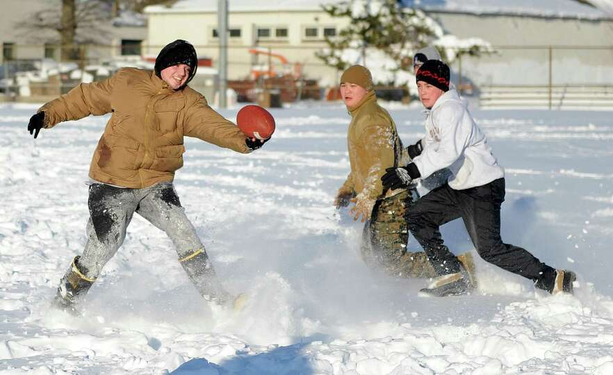 Anthony Pampena Jr., left, Bobby Truong, center, and Timothy Mira, right, play football in Cummings