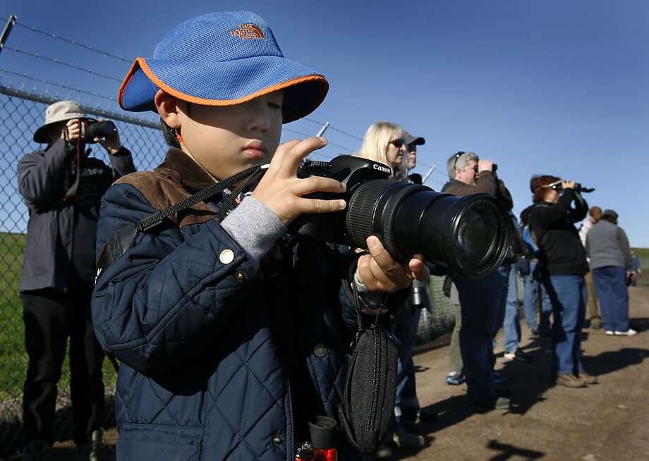 William Oh, 7, checks the settings on his mother's camera before snapping photos of waterfowl on a bird-watching tour at the 17th annual Flyway Festival on Mare Island in Vallejo. Photo: Paul Chinn, The Chronicle