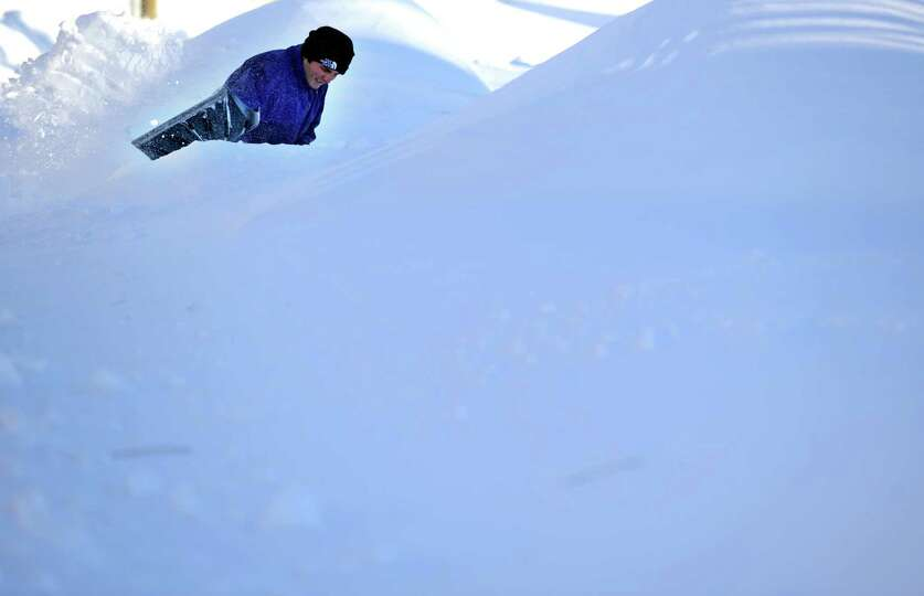 Haci Demir tries to find his car buried beneath the snow in Derby, Conn. Saturday, Feb. 9, 2013 foll