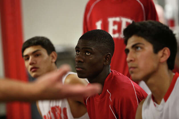 Lee High School's Farah Yussuf listens to his coach, Norm Galyon, with his teammates in the locker room after their game against Reagan in San Antonio on Friday, Jan. 25, 2013. Yussuf came to the San Antonio from a refugee camp in Kenya with his family, who were Somali Bantu refugees, in 2004. Photo: Lisa Krantz, Express-News / © 2012 San Antonio Express-News