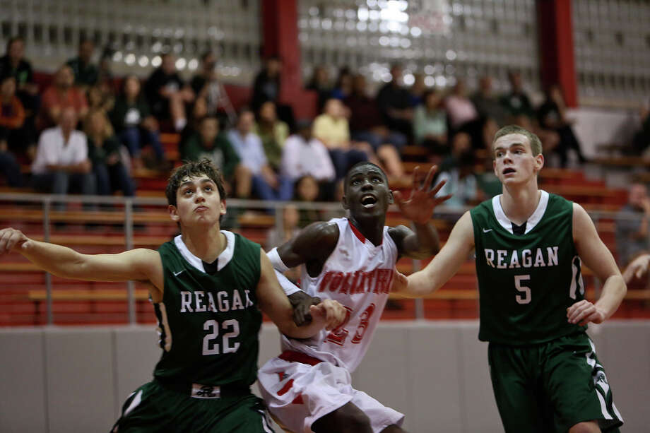 Lee High School's Farah Yussuf, center, waits for the rebound with Reagan's Carter Snape, left, and Liam Bolster, right, during their game in San Antonio on Friday, Jan. 25, 2013. Yussuf came to the San Antonio from a refugee camp in Kenya with his family, who were Somali Bantu refugees, in 2004. Photo: Lisa Krantz, Express-News / © 2012 San Antonio Express-News