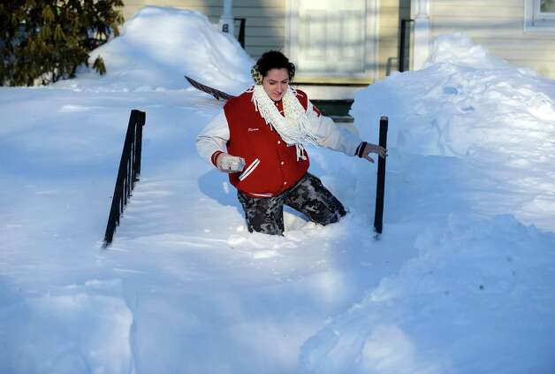 Marisa Conte trudges through the snow in Derby, Conn. to bring her neighbor some eggs Saturday, Feb. 9, 2013 following a severe blizzard that dumped up to three feet of snow across the state. Photo: Autumn Driscoll