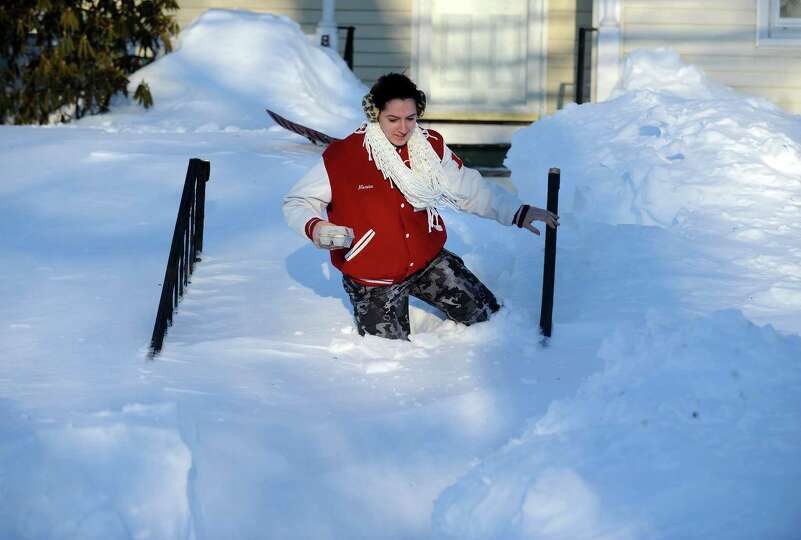 Marisa Conte trudges through the snow in Derby, Conn. to bring her neighbor some eggs Saturday, Feb.