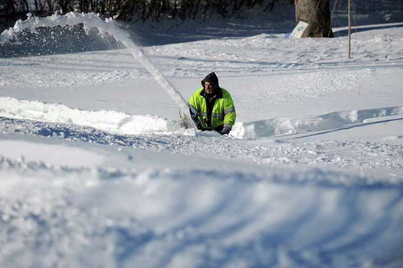 John Sonsini uses a snowblower to clear his sidewalk in Derby, Conn. as residents face massive snow