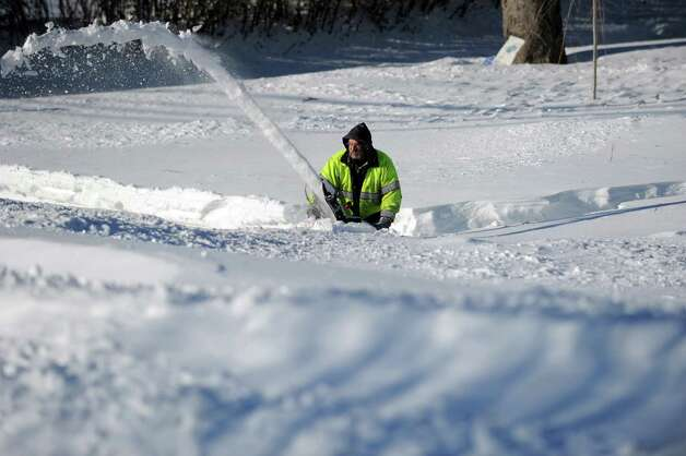 John Sonsini uses a snowblower to clear his sidewalk in Derby, Conn. as residents face massive snow removal Saturday, Feb. 9, 2013 following a severe blizzard that dumped up to three feet of snow across the state.  While Sonsini managed to clear his driveway and walkways, his road still had several feet of snow covering it. Photo: Autumn Driscoll
