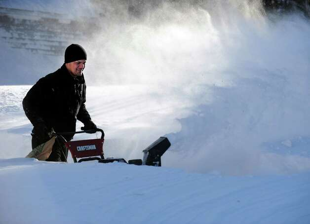 Tony Colon uses a snowblower to clear his driveway in Derby, Conn. as residents face massive snow removal Saturday, Feb. 9, 2013 following a severe blizzard that dumped up to three feet of snow across the state. Photo: Autumn Driscoll