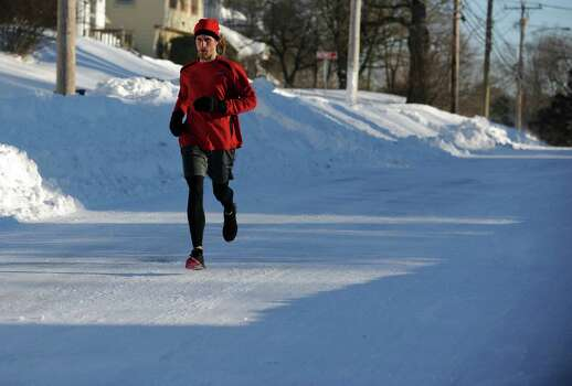 Timothy Milenkevich, of Ansonia, runs down Hawthorne Avenue in Derby, Conn. Saturday, Feb. 9, 2013 following a severe blizzard that dumped up to three feet of snow across the state. Photo: Autumn Driscoll