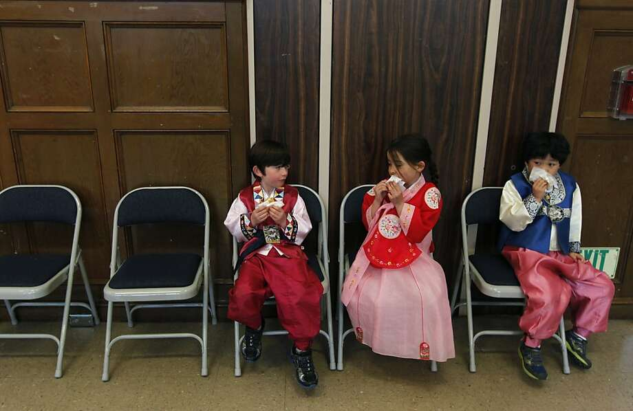 Mica Maggs (left), Grace Sohn (center) and Jooyoung Moon munch on kimchi pancakes at a celebration for Seol Nal, the Korean Lunar New Year, at the Claire Lilienthal School in San Francisco, Calif. on Friday, Feb. 8, 2013. Students in the Korean-immersion program wore traditional hanbok outfits and participated in a variety of activities to celebrate the lunar new year, which begins Sunday. Photo: Paul Chinn, The Chronicle