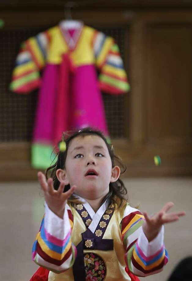Tali Kreutzer Joo learns how to play gonggi, a Korean game similar to jacks, during a celebration of