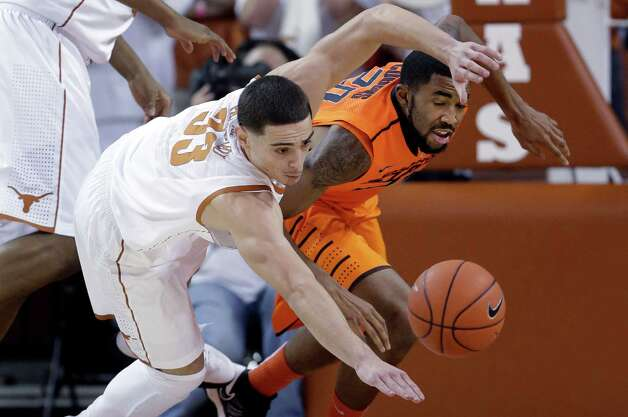 Texas' Ioannis Papapetrou (33) and Oklahoma State's Michael Cobbins, right, scramble for a loose ball during the first half of an NCAA college basketball game, Saturday, Feb. 9, 2013, in Austin, Texas. (AP Photo/Eric Gay) Photo: Eric Gay, Associated Press / AP