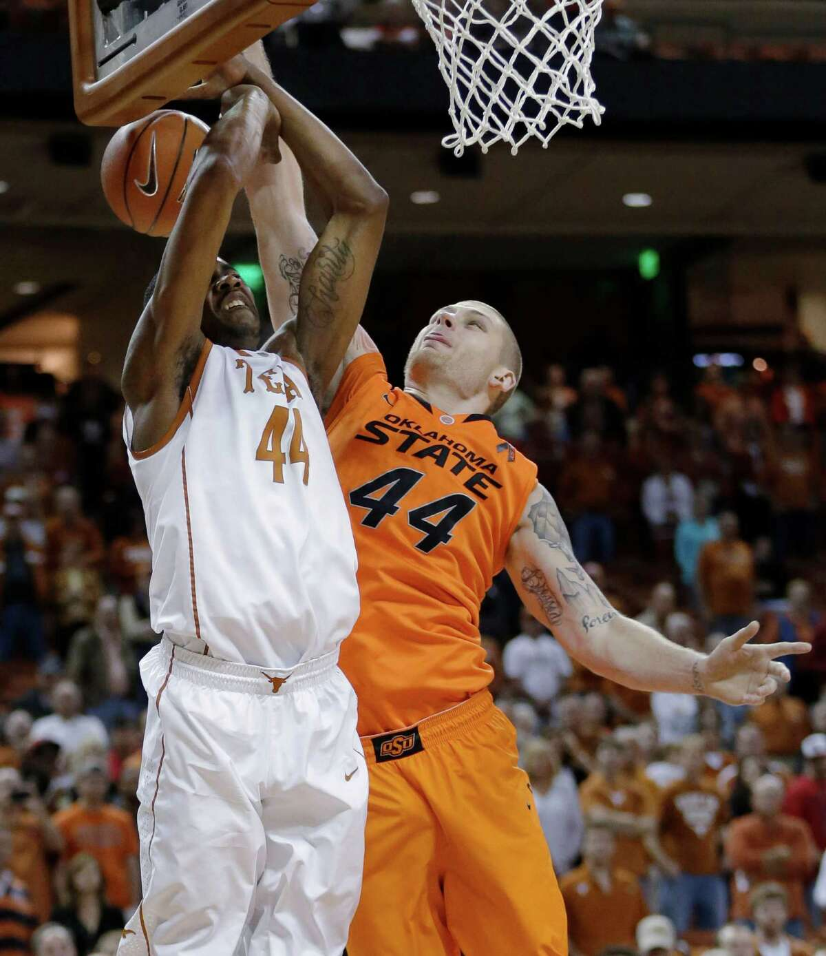 Texas' Prince Ibeh, left, is blocked by Oklahoma State defender Philip Jurick, right, as he tries to score during the first half of an NCAA college basketball game, Saturday, Feb. 9, 2013, in Austin, Texas. (AP Photo/Eric Gay)