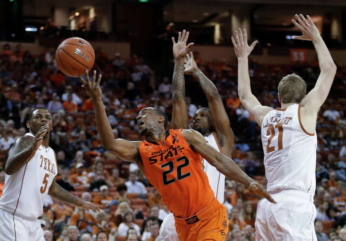 Oklahoma State's Markel Brown (22) shoots through Texas defenders Jaylen Bond (5), Connor Lammert (21) and Julien Lewis, center, during the second half of an NCAA college basketball game, Saturday, Feb. 9, 2013, in Austin, Texas. Oklahoma State won 72-59. (AP Photo/Eric Gay)