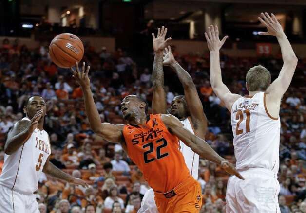Oklahoma State's Markel Brown (22) shoots through Texas defenders Jaylen Bond (5), Connor Lammert (21) and Julien Lewis, center, during the second half of an NCAA college basketball game, Saturday, Feb. 9, 2013, in Austin, Texas. Oklahoma State won 72-59. (AP Photo/Eric Gay) Photo: Eric Gay, Associated Press / AP