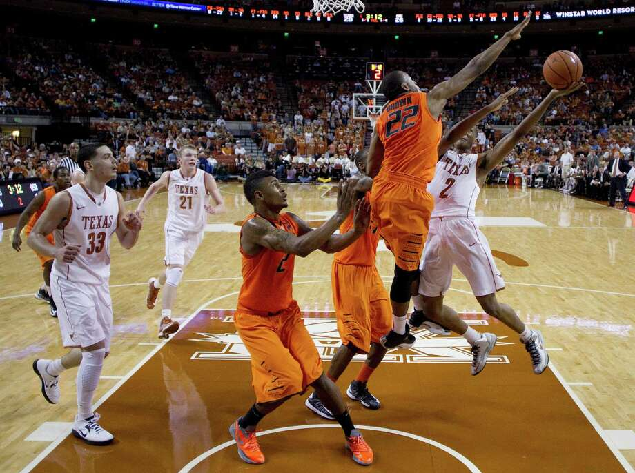 Texas' Demarcus Holland (2) shoots as Oklahoma State's Markel Brown (22), Le'Bryan Nash (2) and Kamari Murphy, center, defend during the first half of an NCAA college basketball game, Saturday, Feb. 9, 2013, in Austin, Texas. (AP Photo/Eric Gay) Photo: Eric Gay, Associated Press / AP
