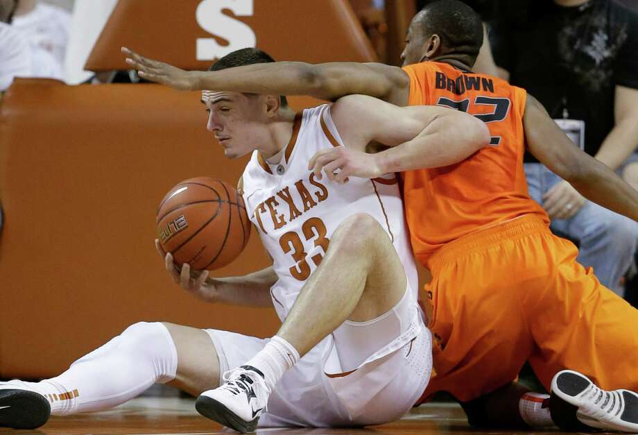 Texas' Ioannis Papapetrou (33) and Oklahoma State's Markel Brown, right, scramble for a loose ball during the first half of an NCAA college basketball game, Saturday, Feb. 9, 2013, in Austin, Texas. (AP Photo/Eric Gay) Photo: Eric Gay, Associated Press / AP