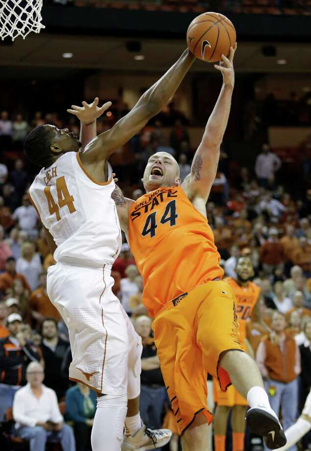 Texas' Prince Ibeh, left, and Oklahoma State's Philip Jurick, right, reach for a rebound during the first half of an NCAA college basketball game, Saturday, Feb. 9, 2013, in Austin, Texas. (AP Photo/Eric Gay) Photo: Eric Gay, Associated Press / AP