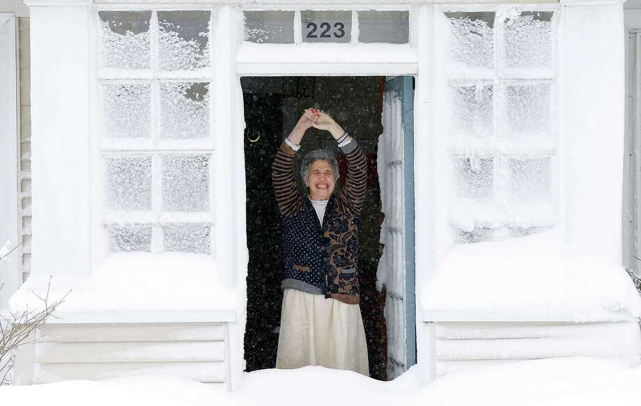 A woman reacts to the snow after opening her front door on February 9, 2013 in Boston, Massachusetts. The powerful storm has knocked out power to 650,000 and dumped more than two feet of snow in parts of New England. Photo: Jared Wickerham, Getty Images / 2013 Getty Images
