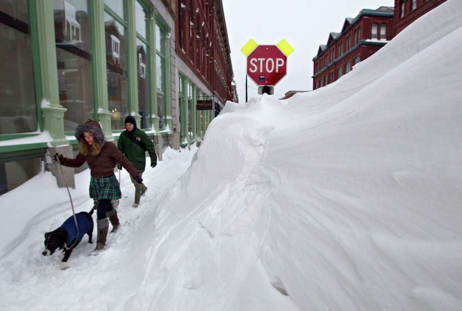 A couple walks past a large snow drift in the Old Port section of Portland, Maine, Saturday, Feb. 9, 2013.  Officials are cautioning residents to stay off the roads in Maine, where Portland set an all-time snowfall record. Photo: Robert F. Bukaty, Associated Press / AP