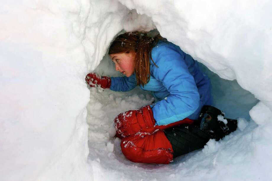 Claire Stout, 12, burrows into a pile of plowed snow near her home in Maplewood, N.J. on Saturday, Feb. 9, 2013. The Northeast storm dumped over a foot of snow in northern N.J. Photo: Rich Schultz, Associated Press / FR27227 AP