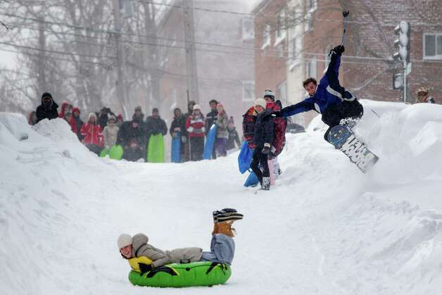 A snowboarder catches air as a resident sleds down the street after Winter Storm Nemo in Boston, Massachusetts, U.S., on Saturday, Feb. 9, 2013. More than two feet of snow fell on parts of the U.S. Northeast as high winds left hundreds of thousands of people in the region without power, closed highways and forced the cancellation of 4,700 flights. Photo: Scott Eisen, Bloomberg / © 2013 Bloomberg Finance LP