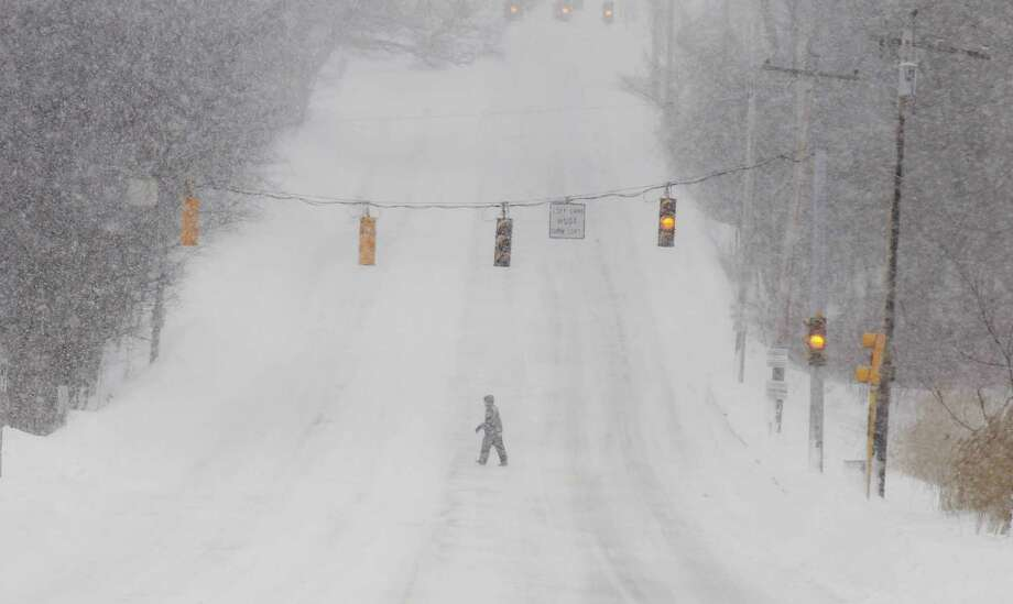 A pedestrian crosses a deserted street in North Andover, Mass. Saturday, Feb. 9, 2013 after a snowstorm came through dumping more than 2 feet of snow on New England. Photo: Winslow Townson, Associated Press / FR170221 AP