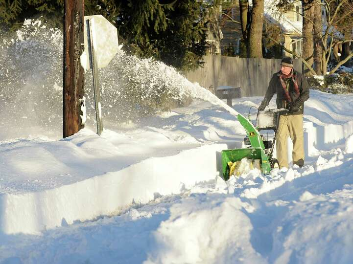 Jeff Norton uses a snow blower to clear Melody Lane in Fairfield, Conn. on Friday, Feb. 9, 2013. The