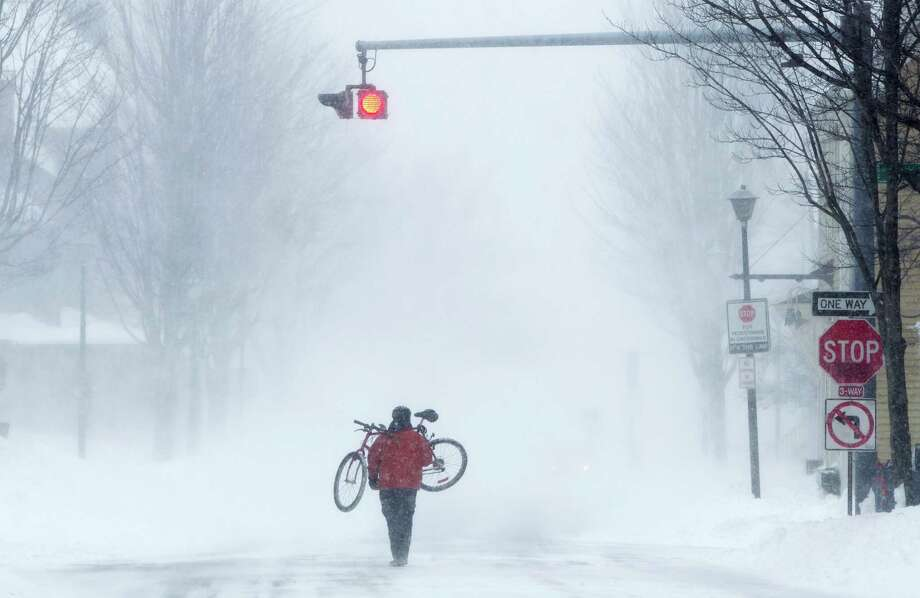 Juan Tavares carries his bike rather than risk riding on a snow-covered street during a blizzard, Saturday, Feb. 9, 2013, in Portland, Maine. The storm dumped more than 30 inches of snow as of Saturday afternoon, breaking the record for the biggest storm on record. Photo: Robert F. Bukaty, Associated Press / AP