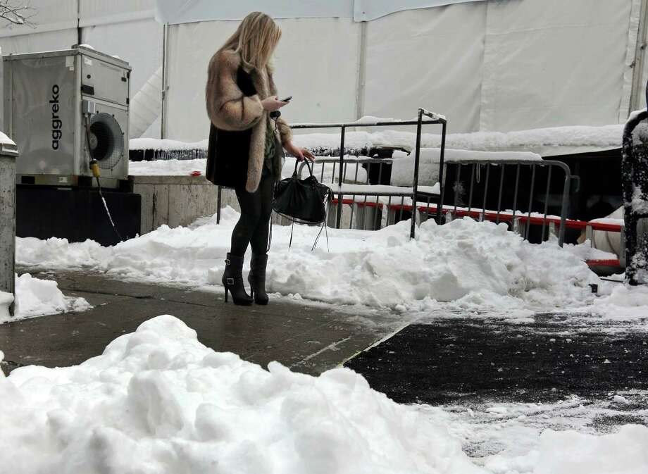 A woman checks her mobile phone outside Lincoln Center, home of New York's Fashion Week shows, Saturday, Feb. 9, 2013. In New York City, the snow total in Central Park was 8.1 inches by 3 a.m. Photo: Richard Drew, Associated Press / AP