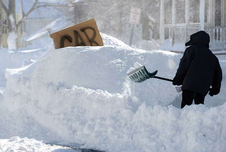 A boy digs around a car marked with a sign on a street in Windsor Locks, Conn., Saturday, Feb. 9, 2013. A behemoth storm packing hurricane-force wind gusts and blizzard conditions swept through the Northeast overnight. Photo: Jessica Hill, Associated Press / FR125654 AP