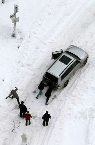 People attempt to push a stuck vehicle in the Back Bay neighborhood following a powerful blizzard on February 9, 2013 in Boston, Massachusetts. The storm knocked out power to 650,000 and dumped more than two feet of snow in parts of New England. Photo: Mario Tama, Getty Images / 2013 Getty Images