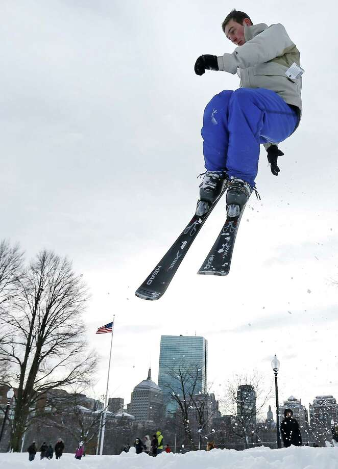 Thomas Kolek, a Northeastern University student from Westford, Mass., spins a helicopter jump while skiing on Boston Common in Boston, Saturday, Feb. 9, 2013.  The Boston area received about two feet of snow from a winter storm. A howling storm across the Northeast left the New York-to-Boston corridor shrouded in 1 to 3 feet of snow Saturday, stranding motorists on highways overnight and piling up drifts so high that some homeowners couldn't get their doors open. More than 650,000 homes and businesses were left without electricity. Photo: Charles Krupa, Associated Press / AP