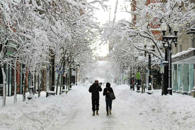 A couple walks down Westminster Street in downtown Providence, R.I., after a winter storm dumped two feet of snow on the area, Saturday, Feb. 9, 2013. Photo: Stew Milne, Associated Press / FR56276 AP