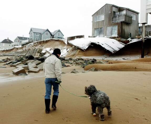 John March walks his dog Grommit past damaged houses along the beach in Plum Island in Newbury, Mass., Saturday, Feb. 9, 2013. Photo: Winslow Townson, Associated Press / FR170221 AP