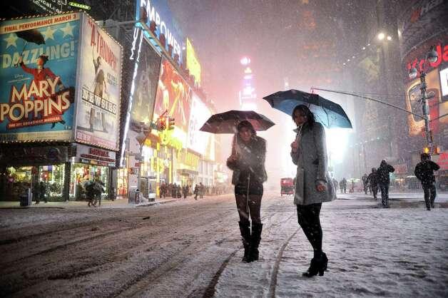 "Two girls look for a taxi in the snow in Times Square in New York on February 8, 2013 during a storm affecting the northeast US. The storm was forecast to bring the heaviest snow to the densely-populated northeast corridor so far this winter, threatening power and transport links for tens of millions of people and the major cities of Boston and New York. New York and other regional airports saw more than 4,500 cancellations ahead of what the National Weather Service called ""a major winter storm with blizzard conditions"" along most of the region's coastline. Photo: MEHDI TAAMALLAH, AFP/Getty Images / Taamallah"