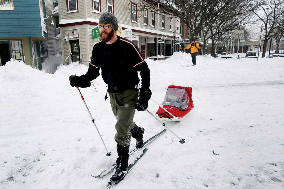 Resident Brian Postlewaite tows his son, Fraser Postlewaite, 2, across Holland Street after Winter Storm Nemo in Somerville, Massachusetts, U.S., on Saturday, Feb. 9, 2013. More than two feet of snow fell on parts of the U.S. Northeast as high winds left hundreds of thousands of people in the region without power, closed highways and forced the cancellation of 4,700 flights. Photo: Kelvin Ma, Bloomberg / © 2013 Bloomberg Finance LP